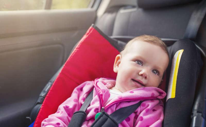 Bebé con sonrisa en silla de bebe, autoasiento